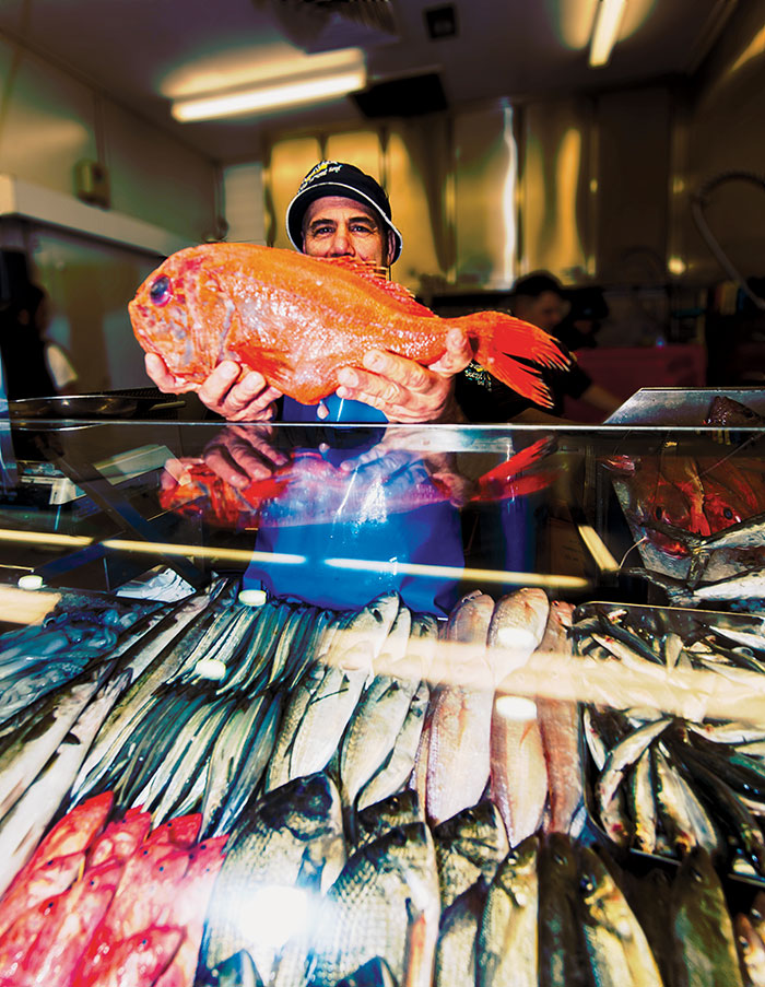 Photo of John Yiannatzis, stallholder at Seafood Oyster Spot, Queen Victoria Market, holding an Orange Roughy