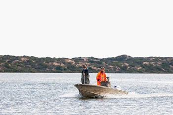Photo of Tucker Sheehan and Glen Hill in a boat on the Coorong lagoon