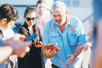 Photo of Jason Simpson and Thi Le discussing a spanner crab